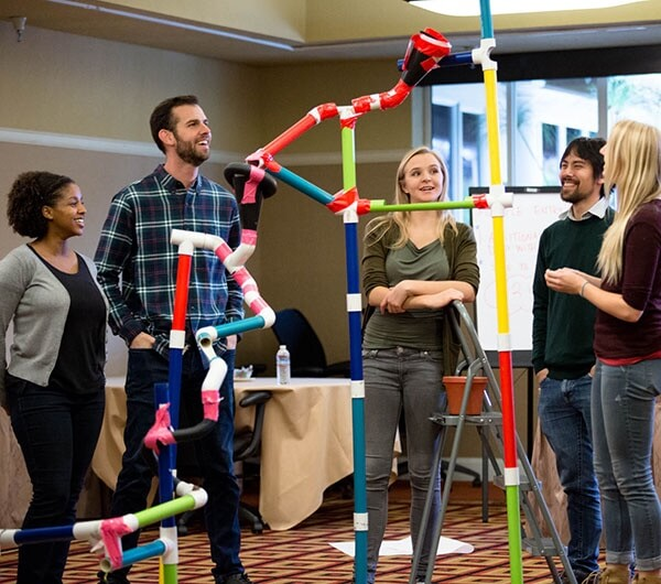 A man stands back and observes the structure he made during team building.