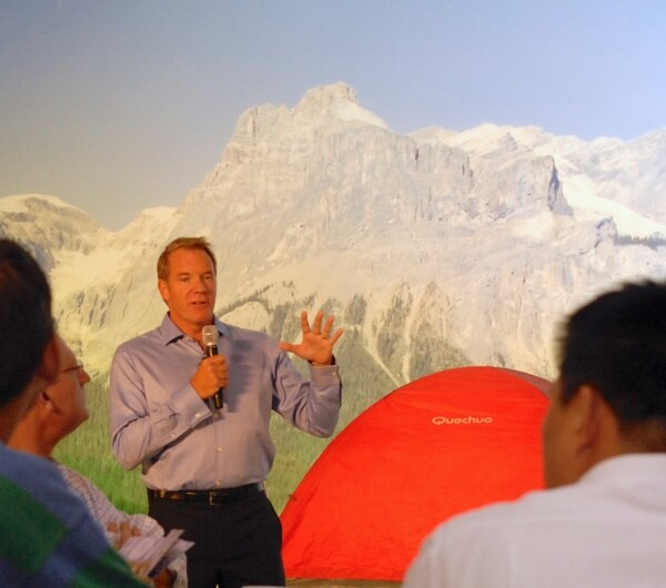 A man in a button-down shirt gives a speech to a room of executives.